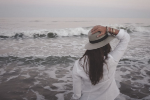 Picture of a woman holding her hat on her head in front of the ocean