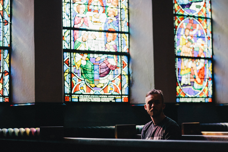Picture of a man sitting in a church pew with stained glass behind him