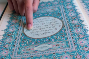 Picture of person reading a passage from the Muslim Koran