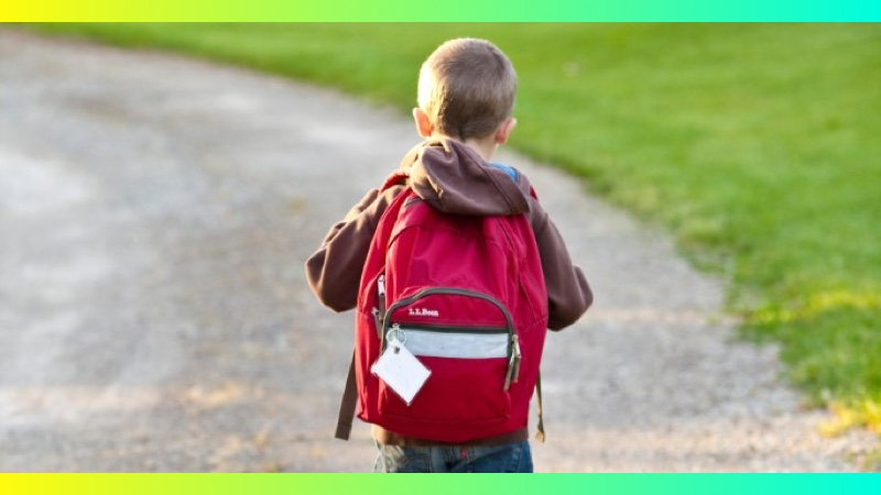 A young boy walking away wearing a red backpack