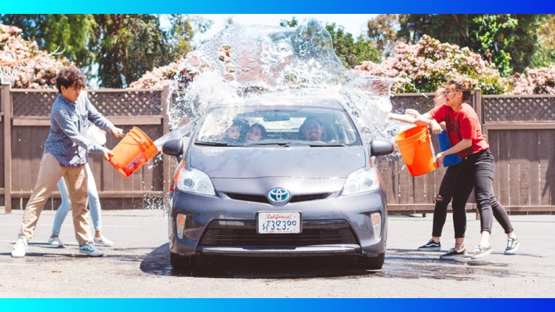 Image of teens splashing a car with water