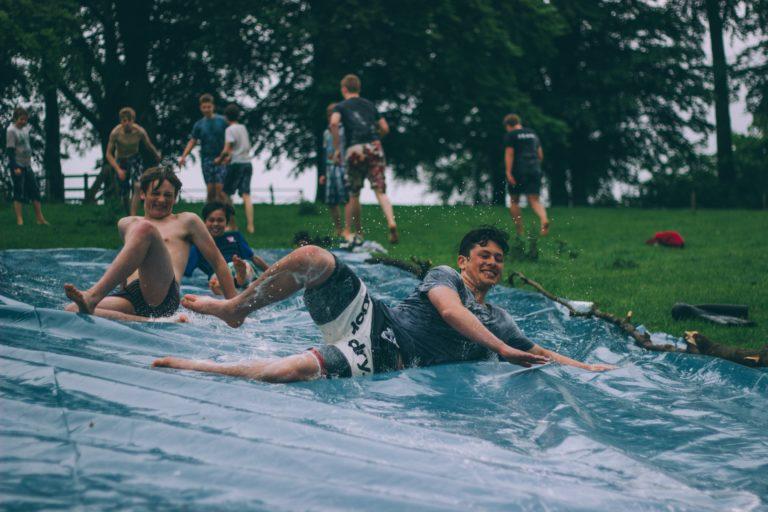 group of boys sliding down a slip-n-slide in the summer
